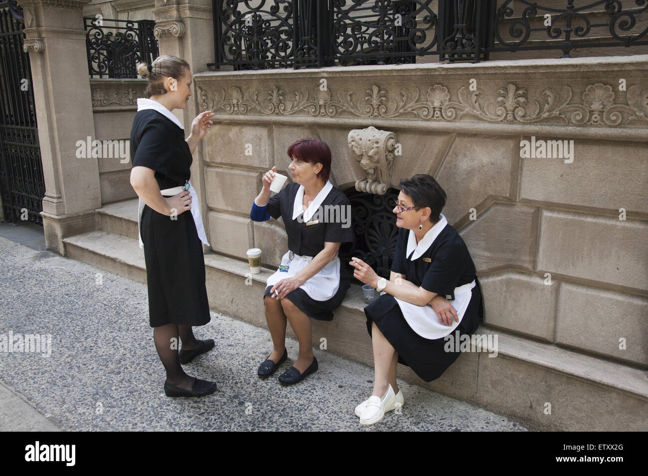 Female workers in their uniforms take a smoking break from work at a  hotel off Madison Ave., NYC - Stock Image