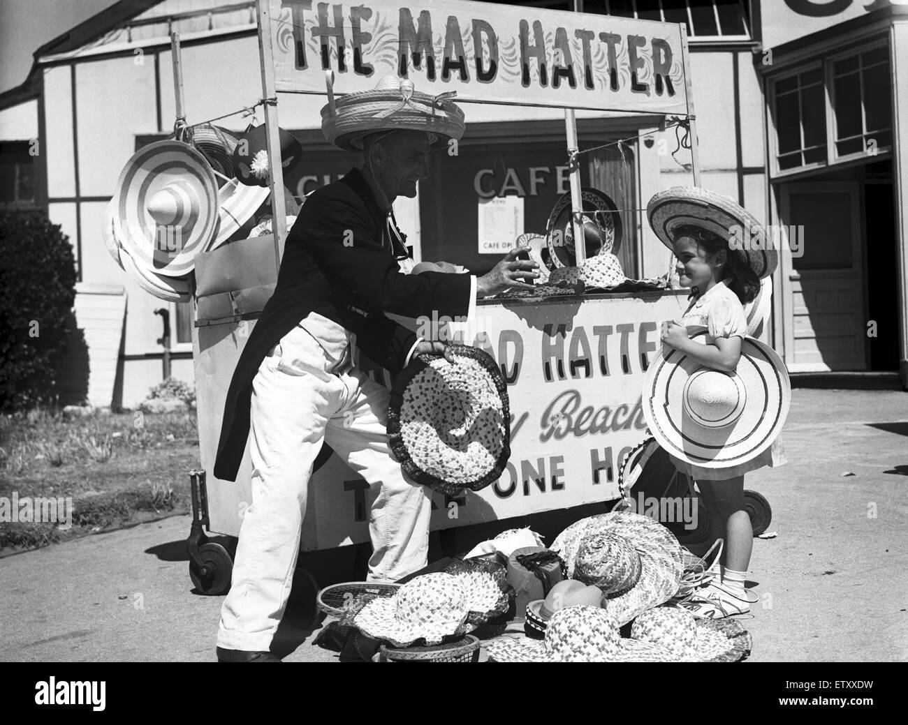 A young girl trying on a hat at 'The Mad Hatter' stall, in Barry Island, Vale of Glamorgan, Wales. 5th August - Stock Image
