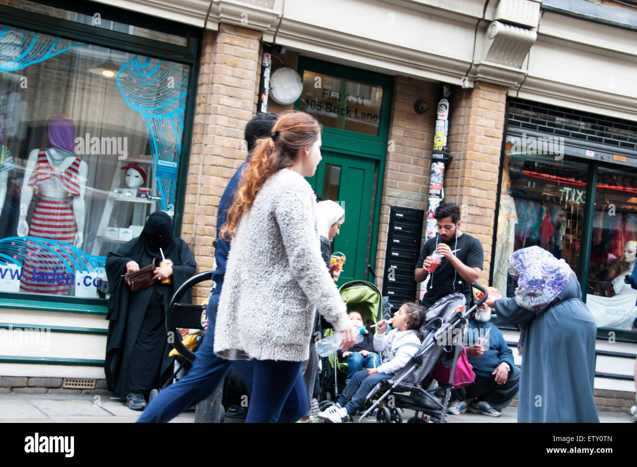 Brick Lane London 2015.On the street, Bangladeshi family and passers by in front of Rokit clothes shop - Stock Image