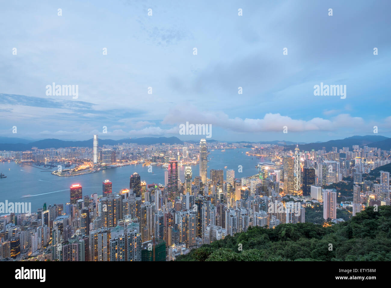 Dusk skyline of Hong Kong and Victoria Harbour from The Peak on a clear day - Stock Image