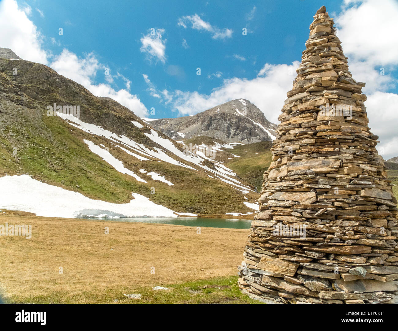 Large stone cairn in the high alps with snowfield and peak - Stock Image
