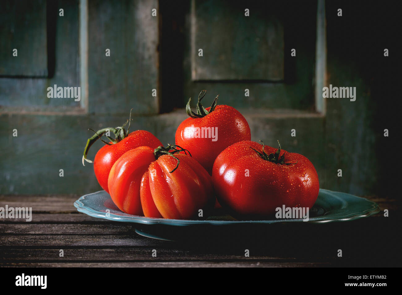Heap of big red tomatoes RAF on turquoise plate over old wooden table. Dark rustic atmosphere - Stock Image