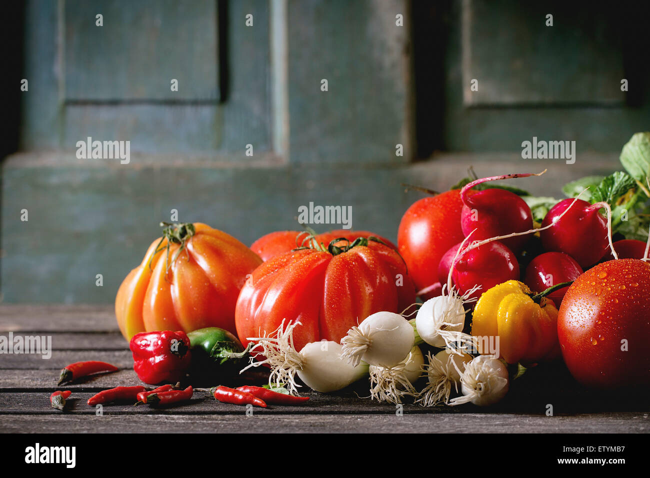 Heap of fresh ripe colorful vegetables tomatoes, chili peppers, green onion and bunch of radish over old wooden - Stock Image