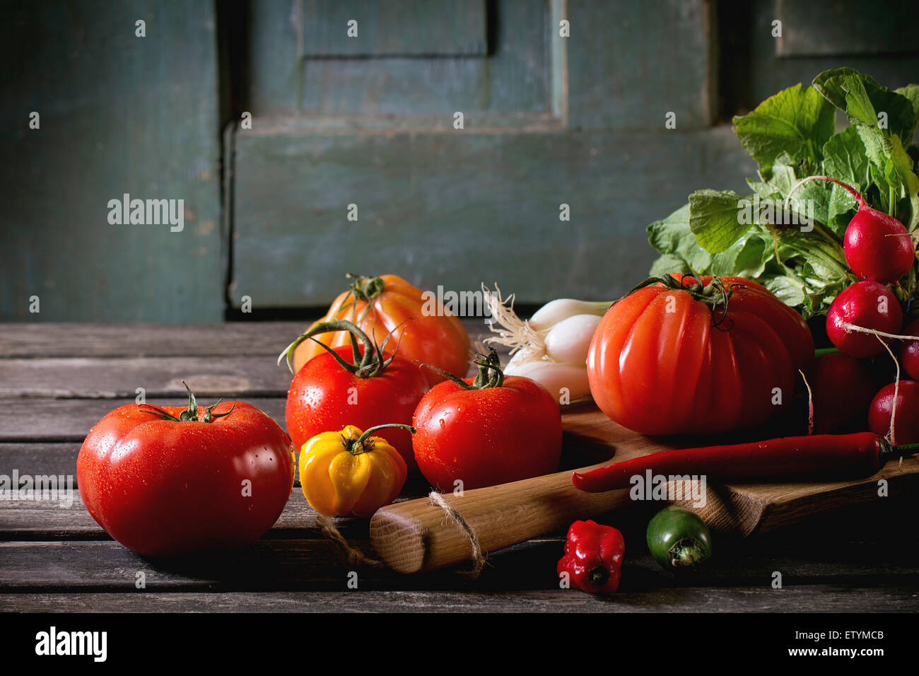 Heap of fresh ripe colorful vegetables tomatoes, chili peppers, green onion and bunch of radish on wooden chopping - Stock Image