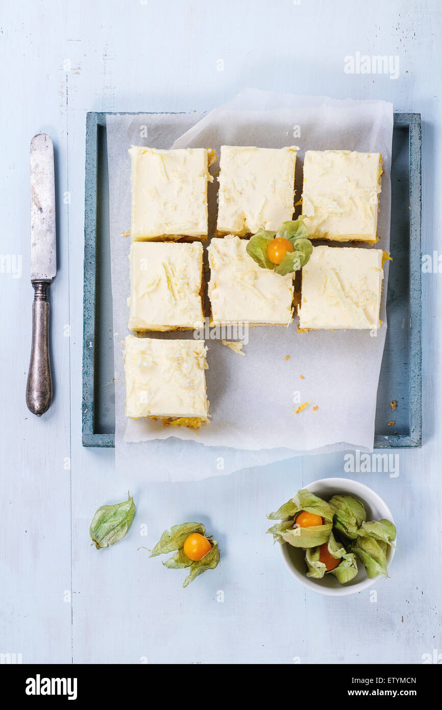 Homemade sliced cake with creamy mousse and tropical fruits mango and physalis served in wooden tray over light - Stock Image