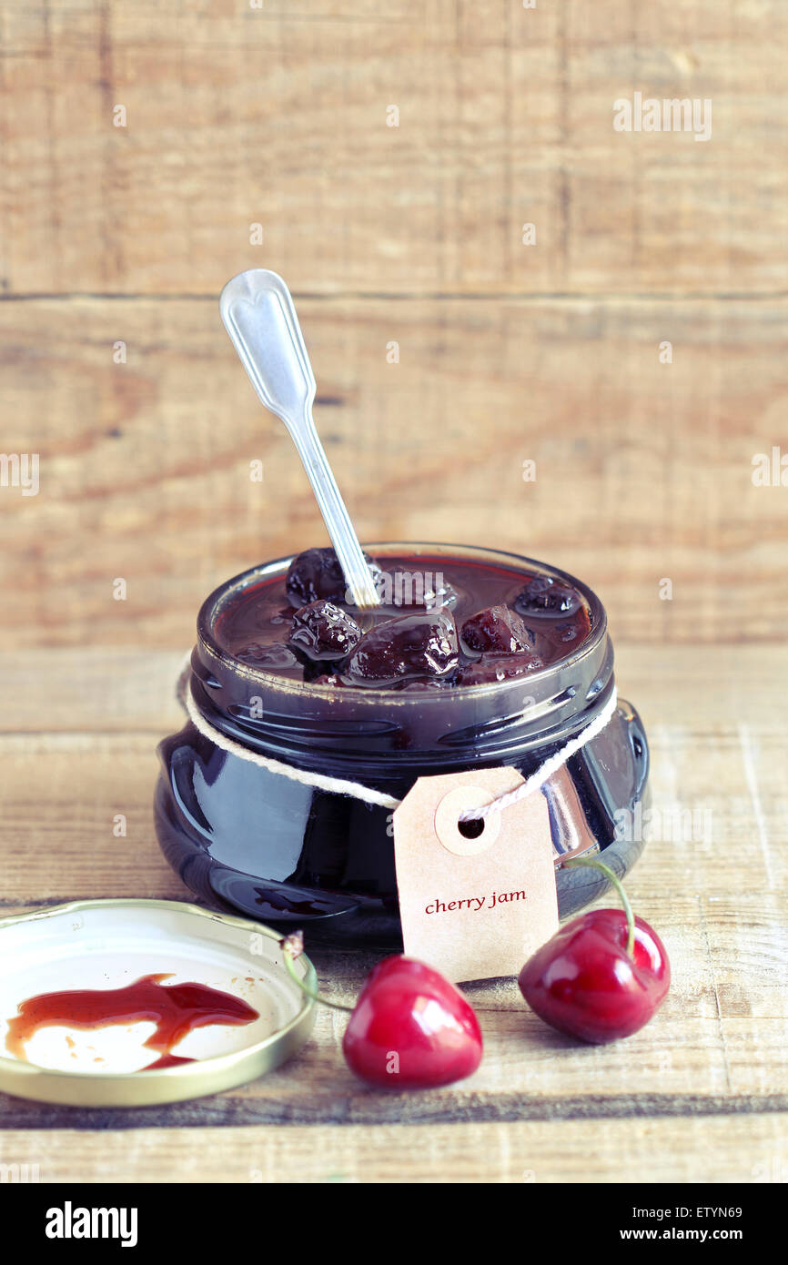 Cherry jam in a glass jar with label - Stock Image