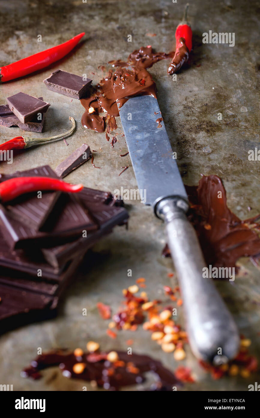 Chopping and melting dark chocolate with fresh and dry red hot chili peppers and vintage knife over old metal background. - Stock Image