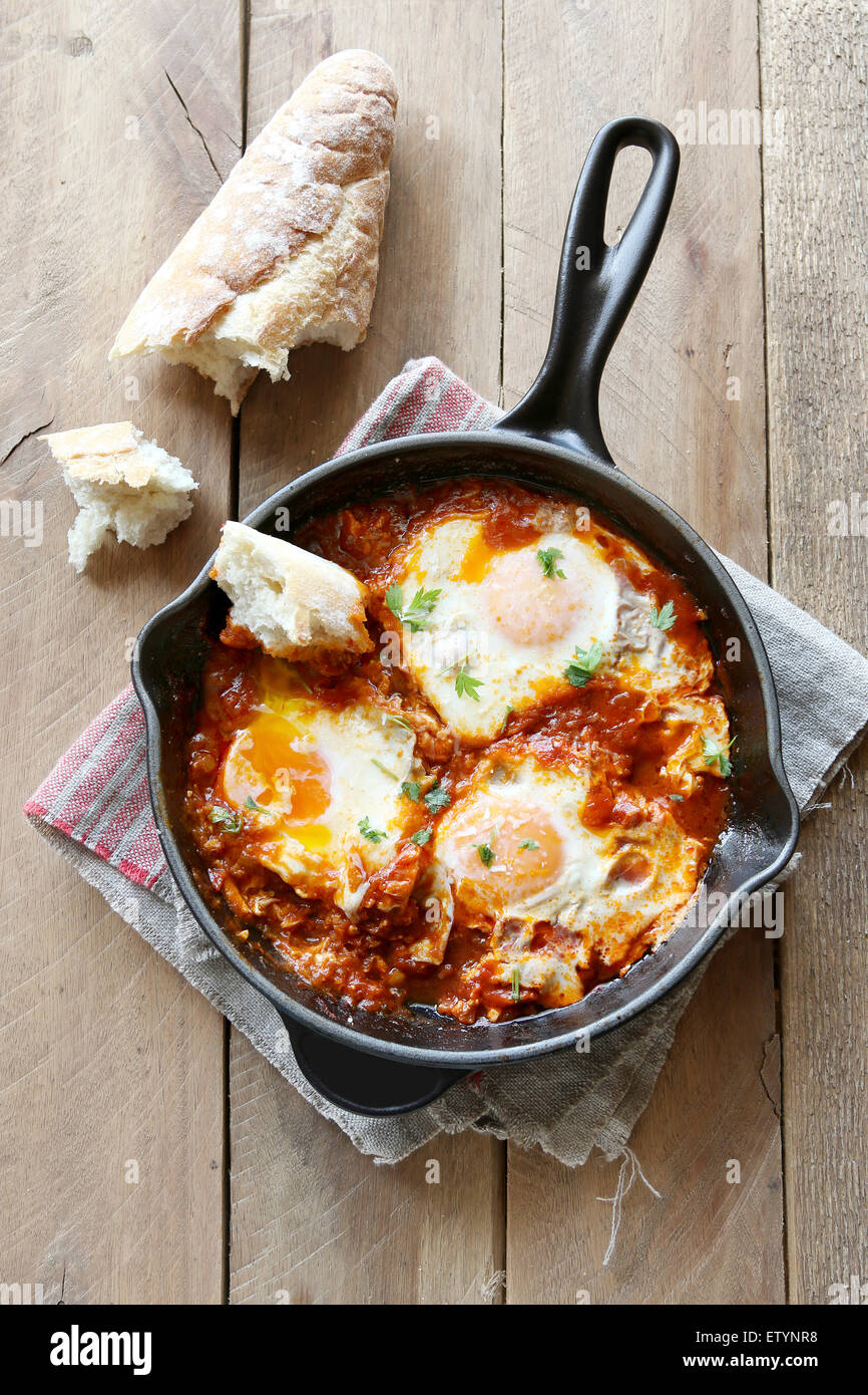 Poached eggs in tomato sauce - Stock Image