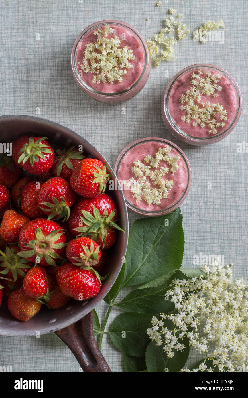 Strawberry creme wit elderberry blossoms on grey patterned background. Top view - Stock Image