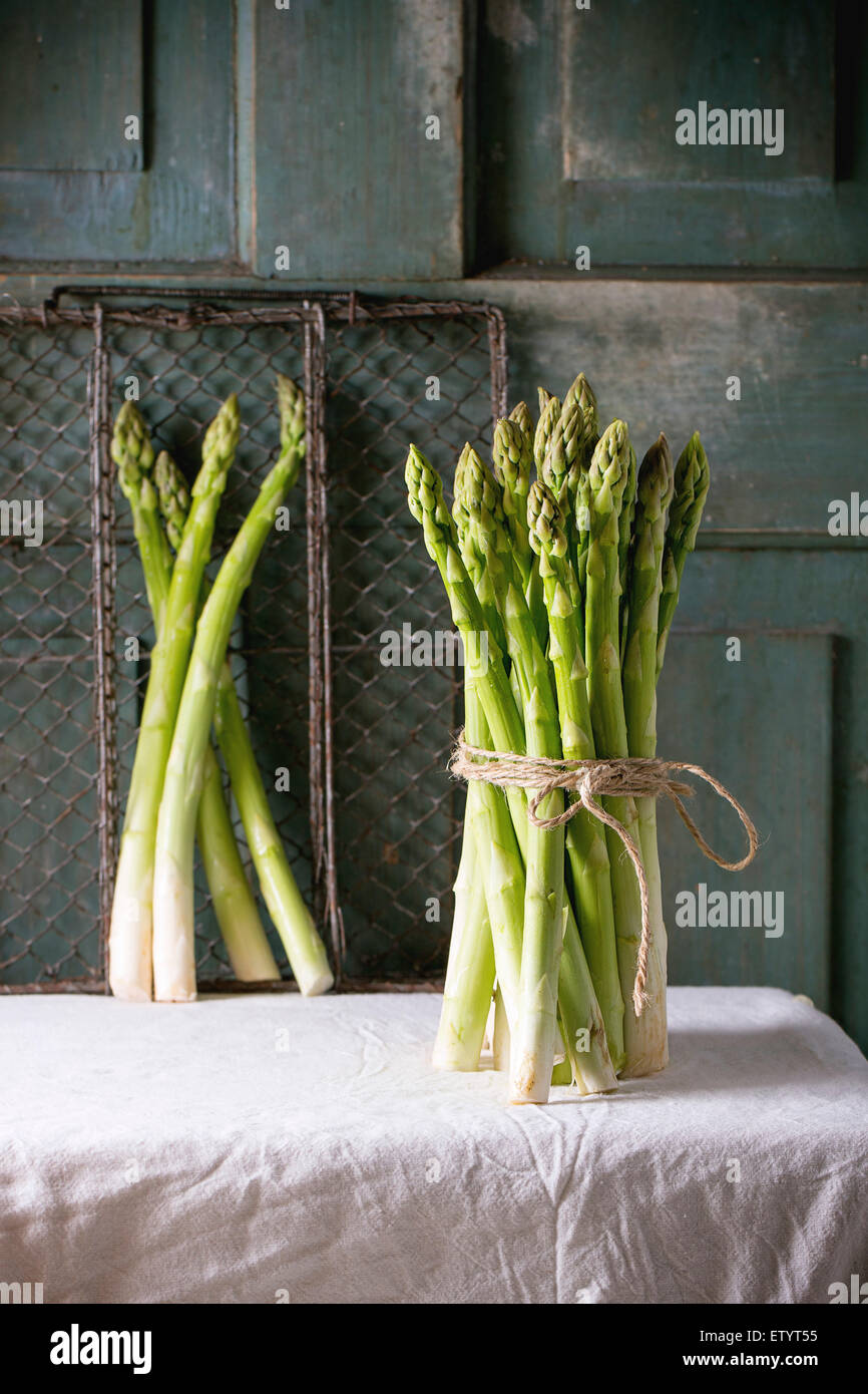 Bundle of green asparagus over white tablecloth with turquoise wooden background. Dark rustic atmosphere - Stock Image