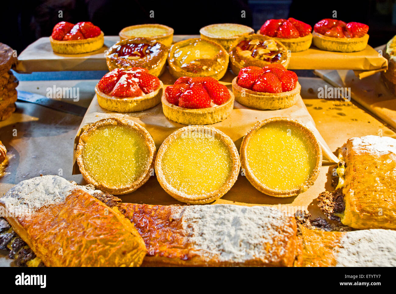 A mouth-watering display of tartlets and other pastries on a food stall at an artisan market in the Tron church, - Stock Image