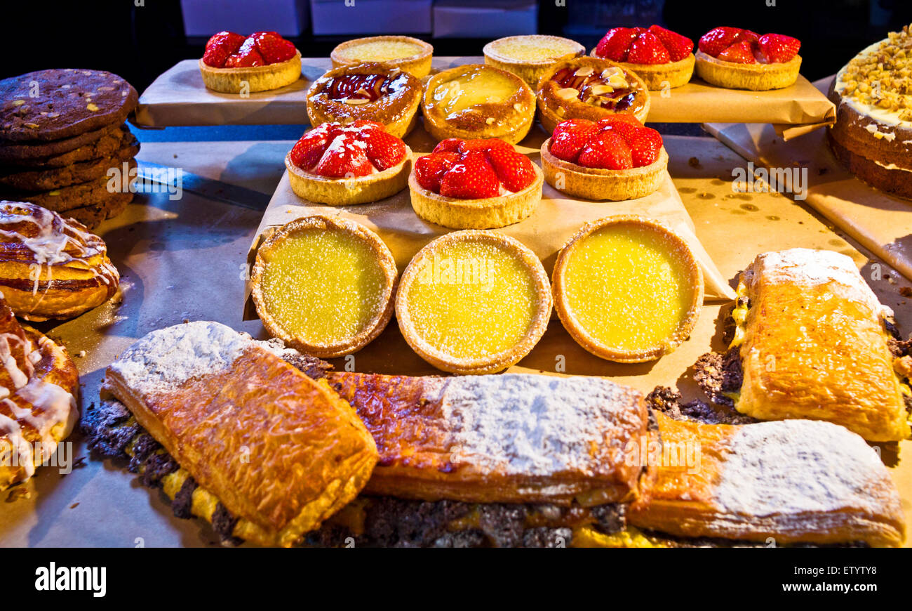 A mouth-watering display of tartlets, pastries and cakes on a food stall at an artisan market in the Tron church, - Stock Image