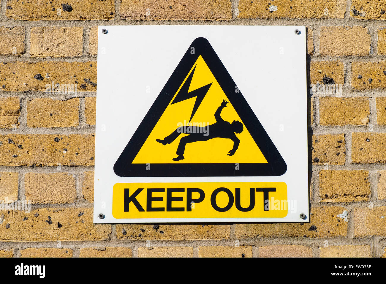 Industrial warning plate in an electricity plant, signaling death danger for high voltage power in the surrounding Stock Photo