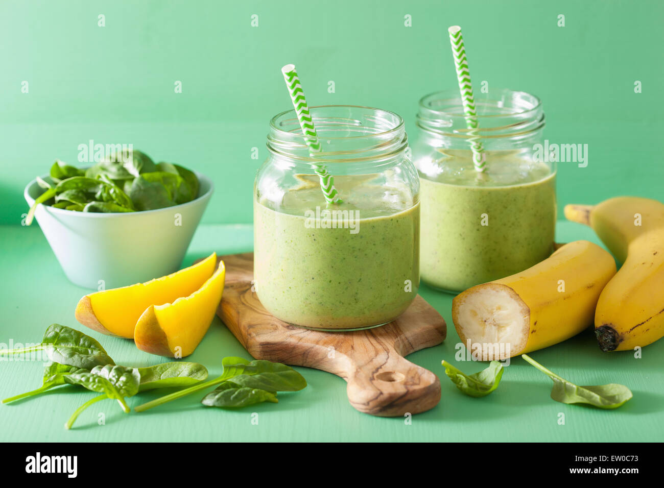healthy green smoothie with spinach mango banana in glass jars - Stock Image