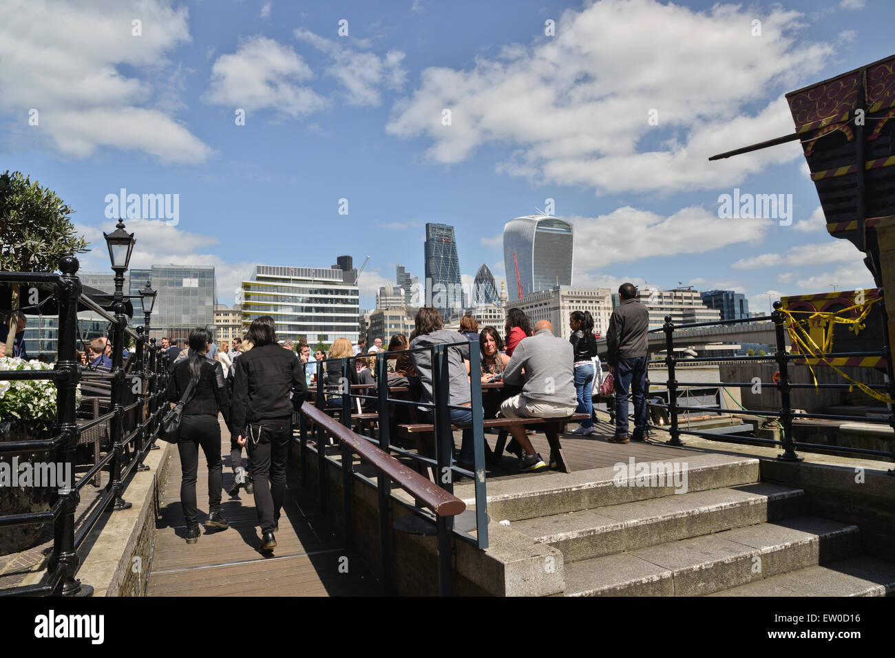 People sitting outside bar with City skyline in background on the banks of the River Thames in Southwark London - Stock Image