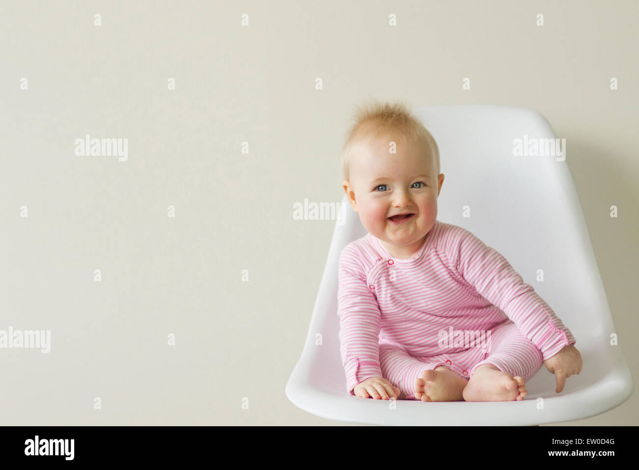 baby girl sitting on white eames chair Stock Photo
