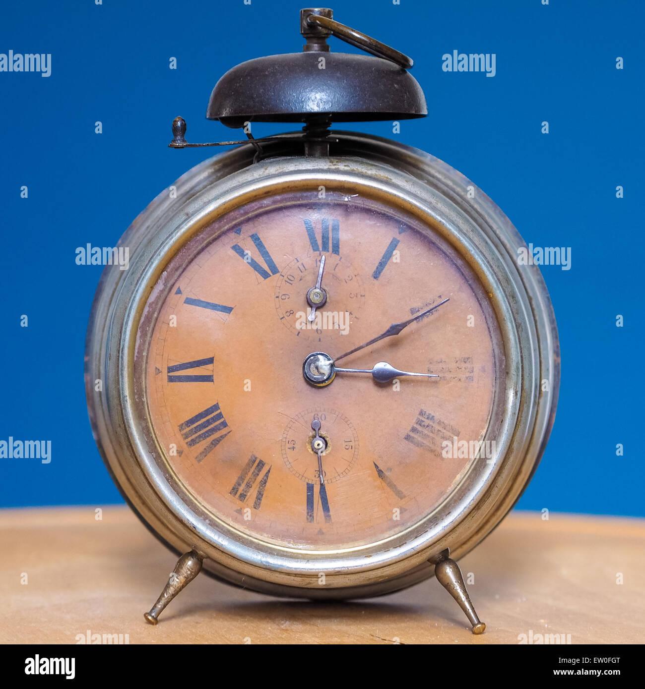 Vintage table alarm clock on wooden desk, retro style. - Stock Image