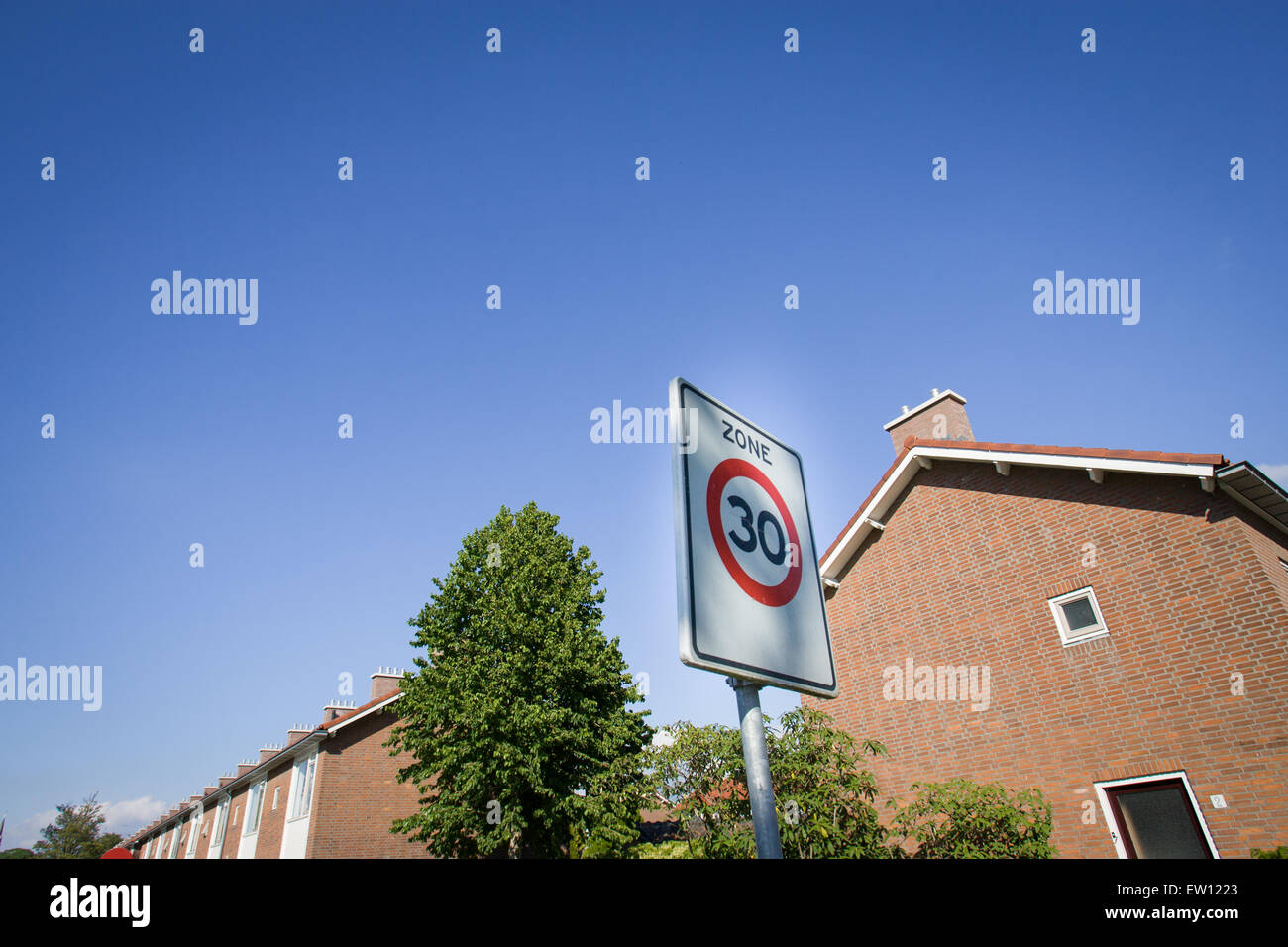 A sign showing a 30 kilometer per hour speed limit in a residential zone is seen. - Stock Image