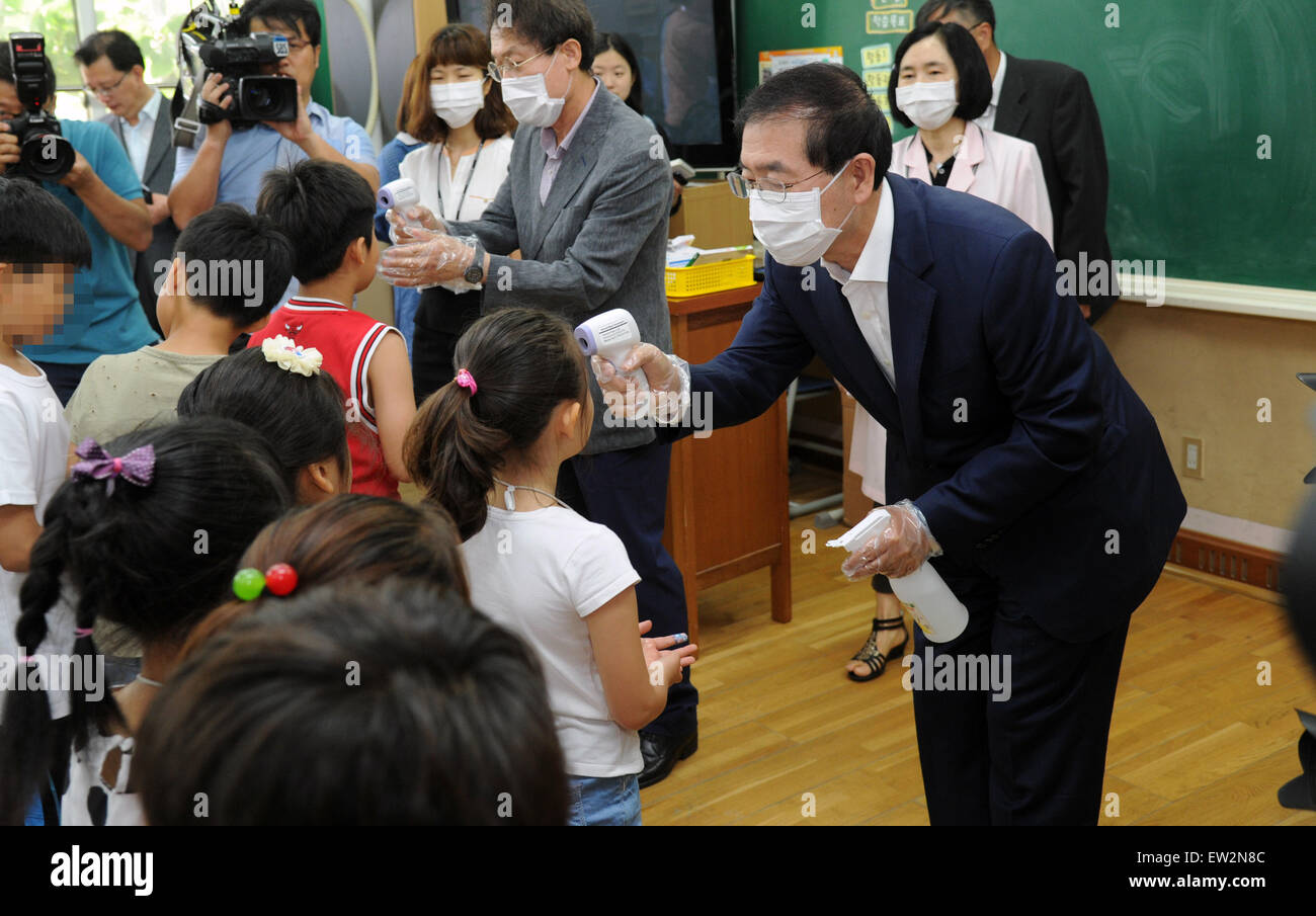 Seoul, South Korea. 17th June, 2015. Seoul Mayor Park Won-soon (R) checks the temperature of a pupil at an elementary Stock Photo