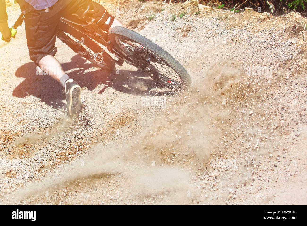 Mountain bike rider drifts through a gravity slope of an artificial downhill track. Gravel sprays upwards. - Stock Image