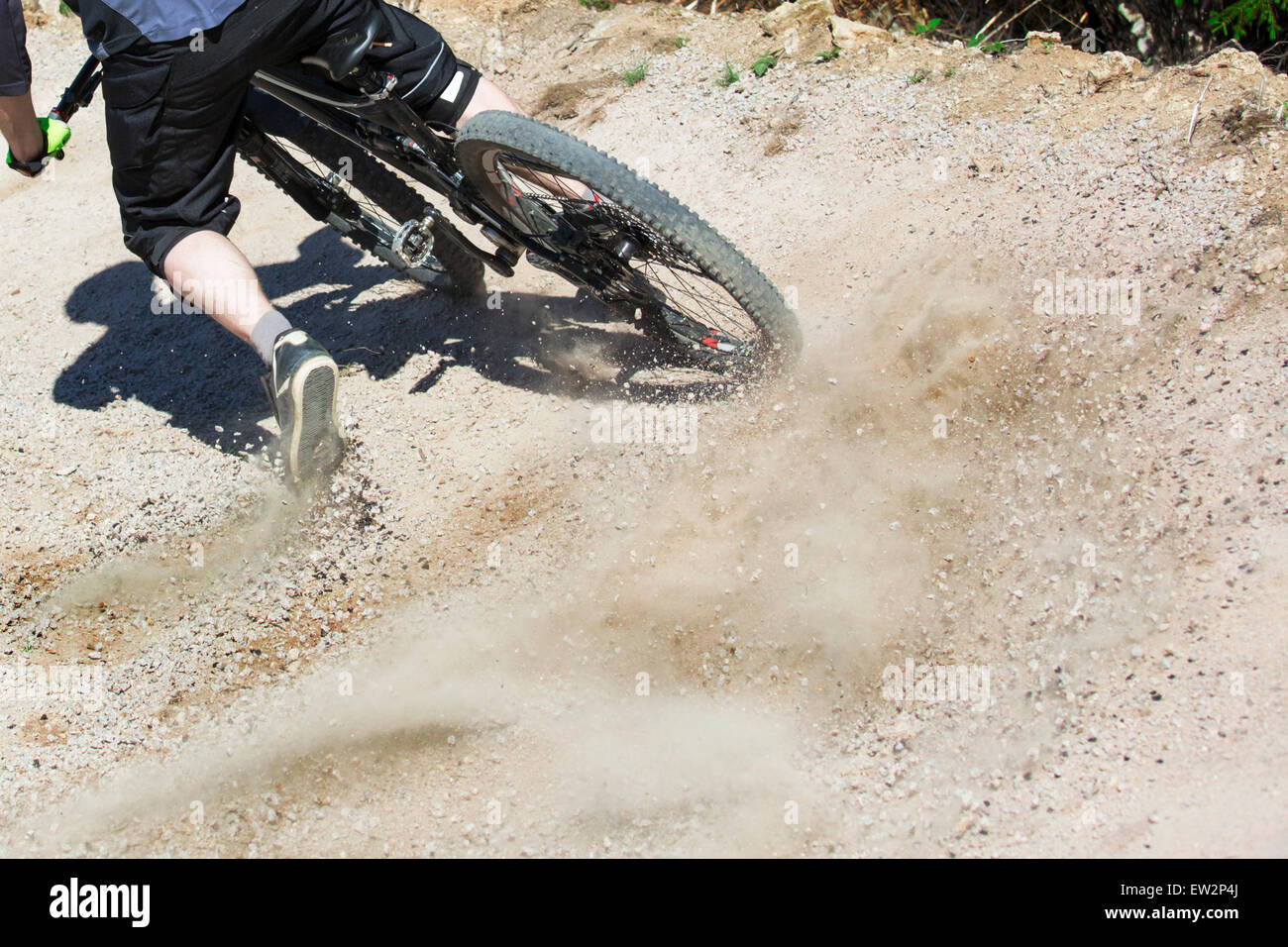 Unfiltered version of mountain bike rider drifting through a gravity slope of an artificial downhill track. Gravel - Stock Image