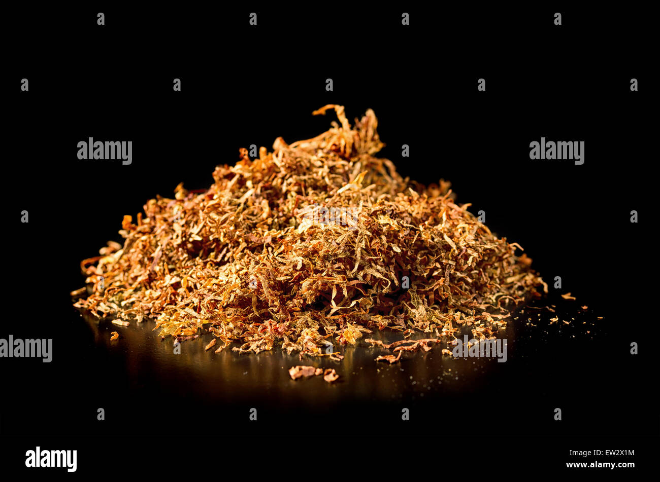 Pile of tobacco on a black background. - Stock Image