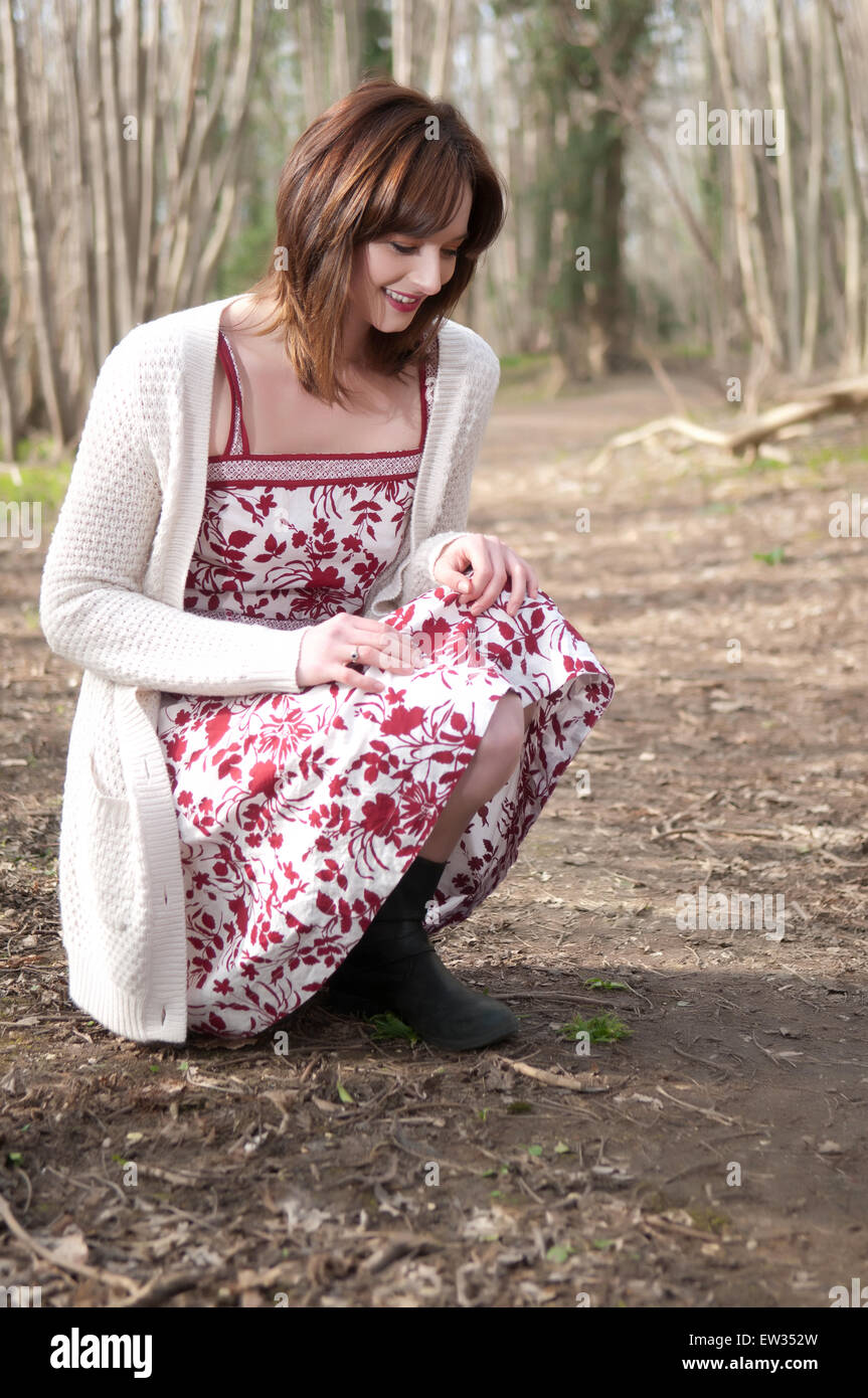 Spring portrait of beautiful young woman in a summer dress and cardigan - Stock Image