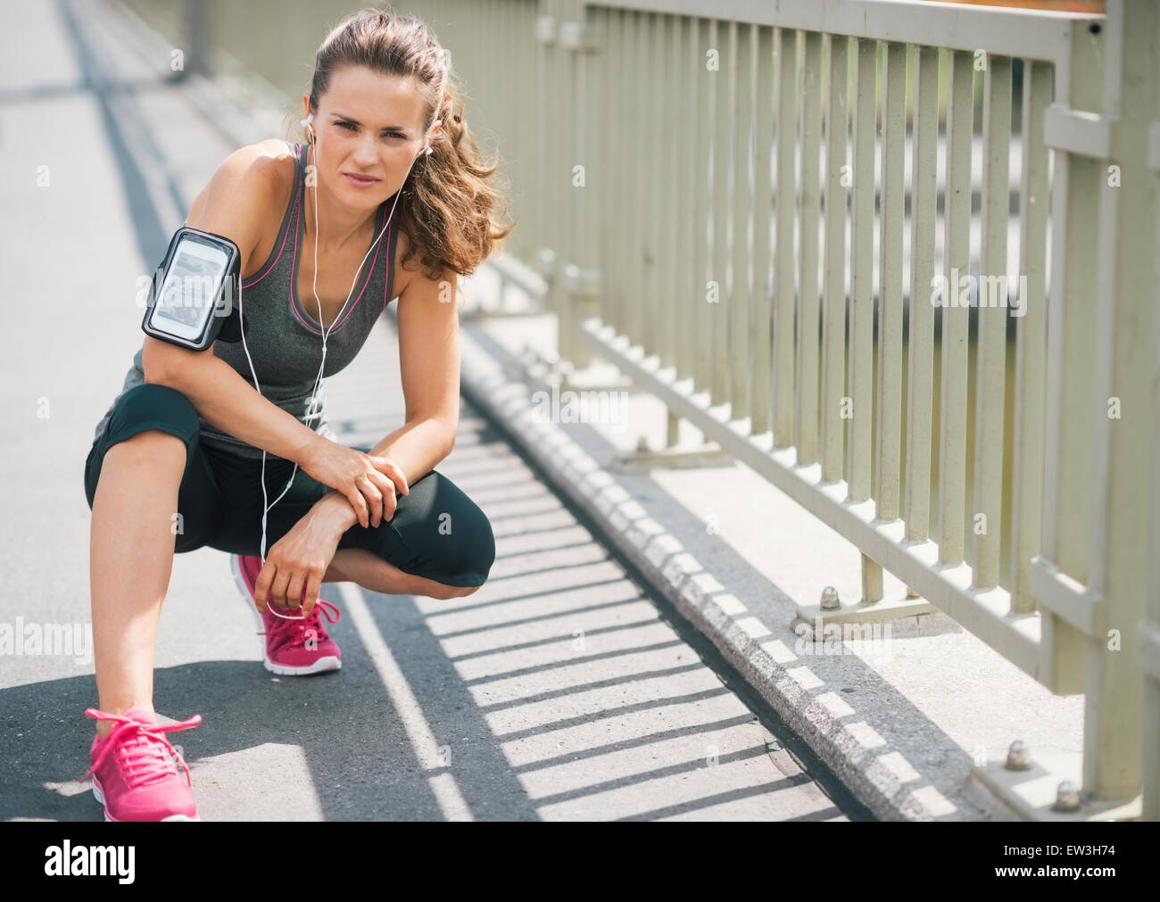 An athletic woman wearing earbuds and her device in a cuff on her arm is getting ready to go on a run. She is looking - Stock Image
