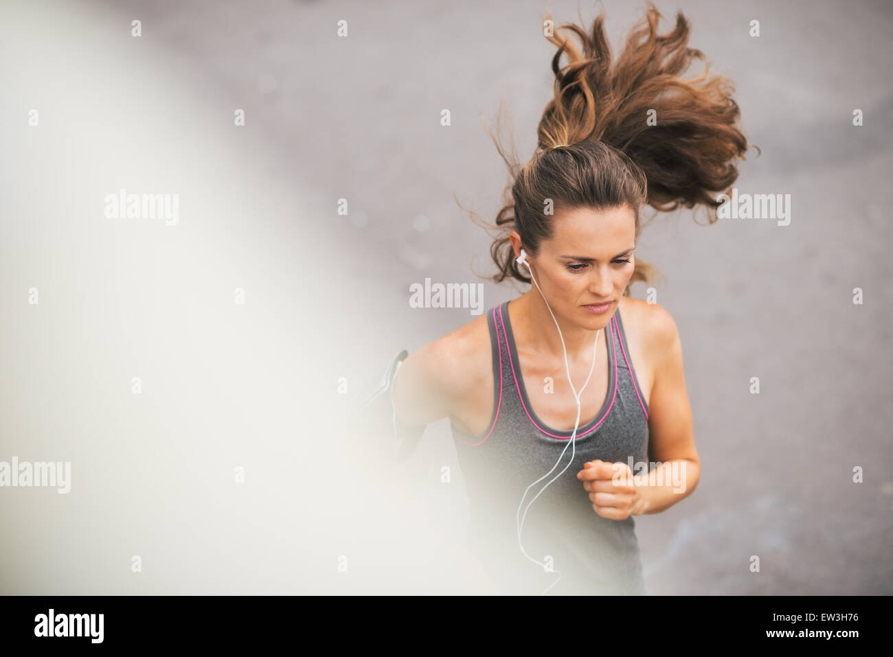 A woman jogger is running, concentrated and in the zone as she listens to music on her earbuds. - Stock Image