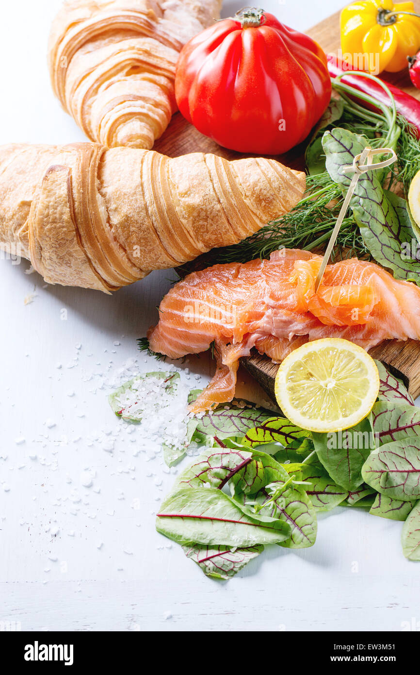 Slaced salted salmon with fresh salad leaves, lemon, sea salt and vegetables, served on wooden chopping board with - Stock Image