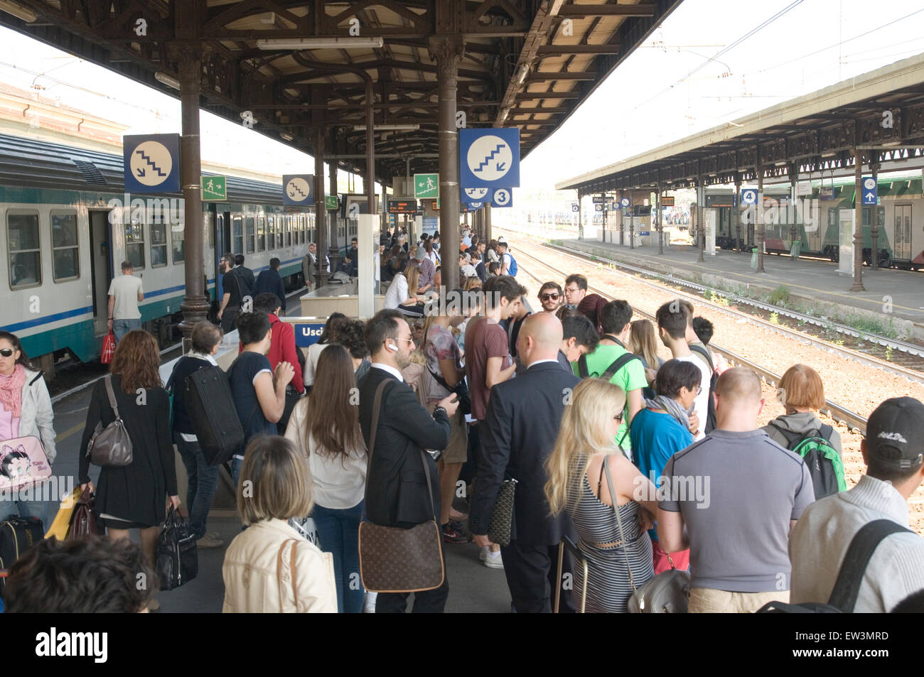 busy packed train station stations platform platforms people commuters commuting italy italian waiting for train - Stock Image