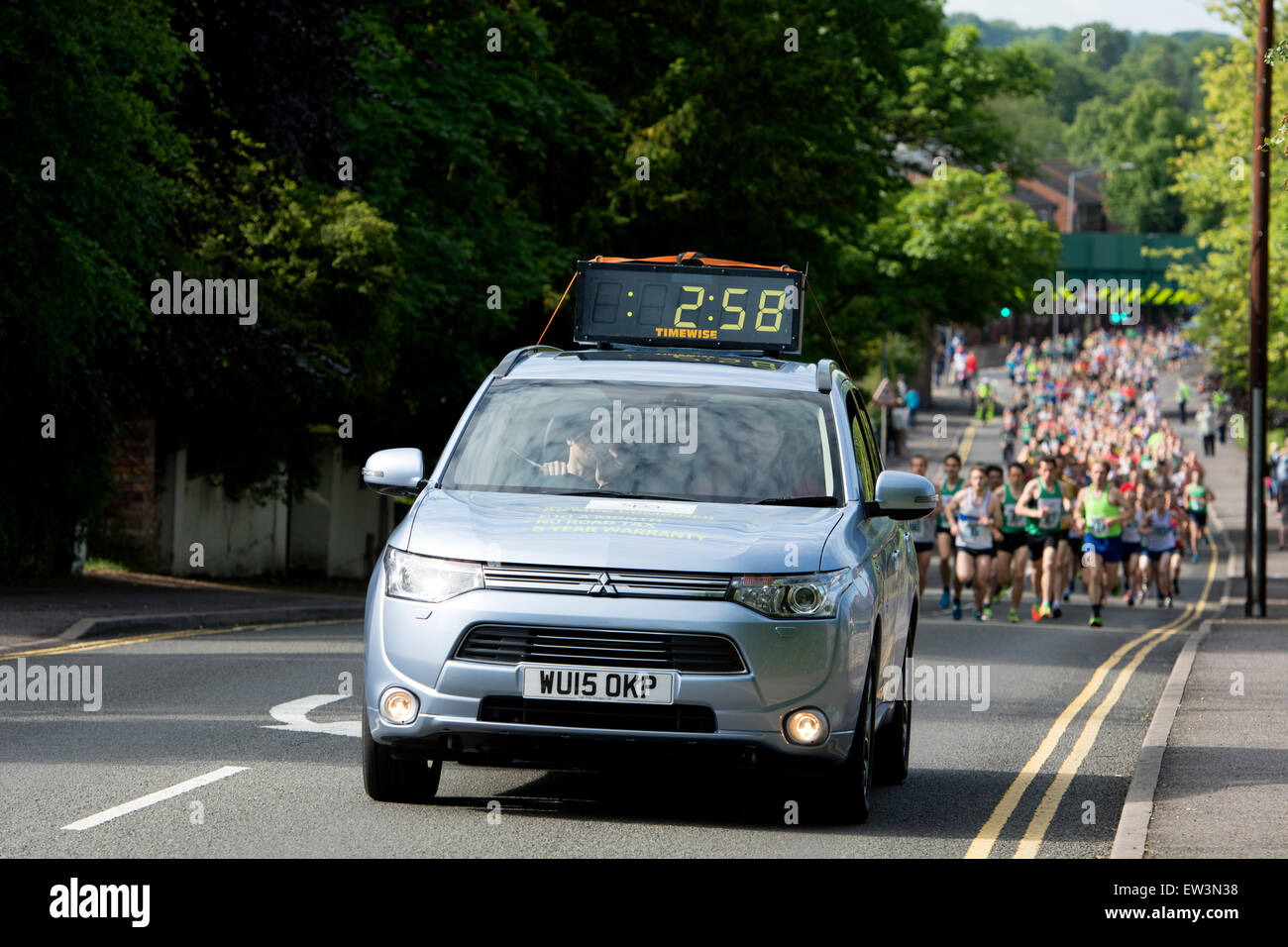 Car with timing clock leading a 10K road race. - Stock Image