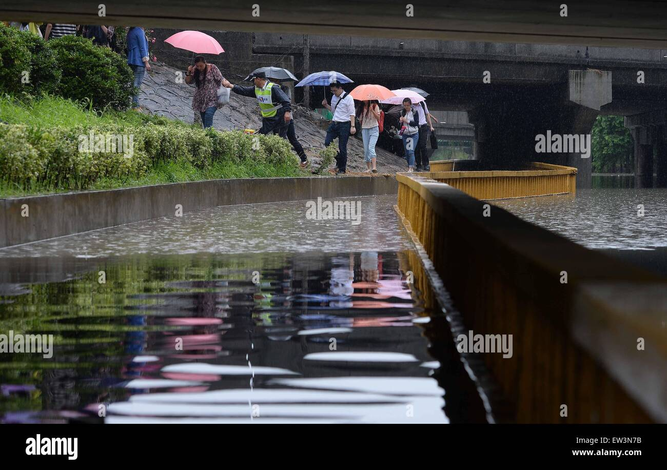 Shanghai, China. 17th June, 2015. Pedestrians are evacuated from a flooded sidewalk in Shanghai, east China, June - Stock Image