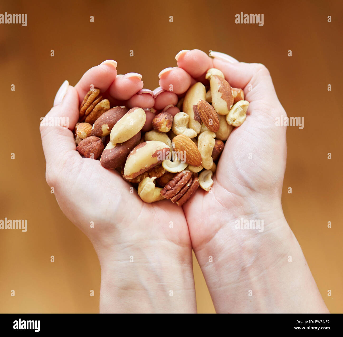 Woman holding a handful of mixed nuts - Stock Image