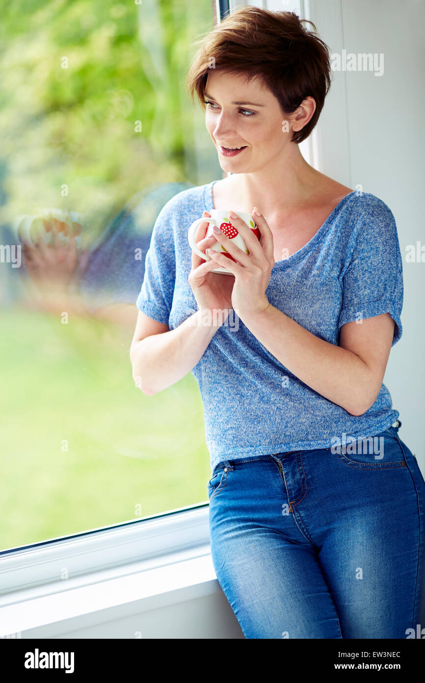 Woman looking out of window - Stock Image