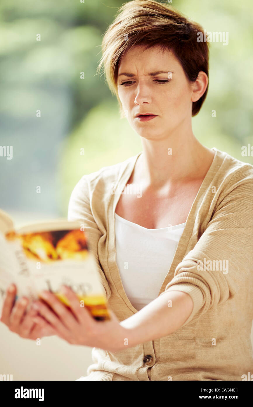 Woman with bad eye sight struggling to read book - Stock Image