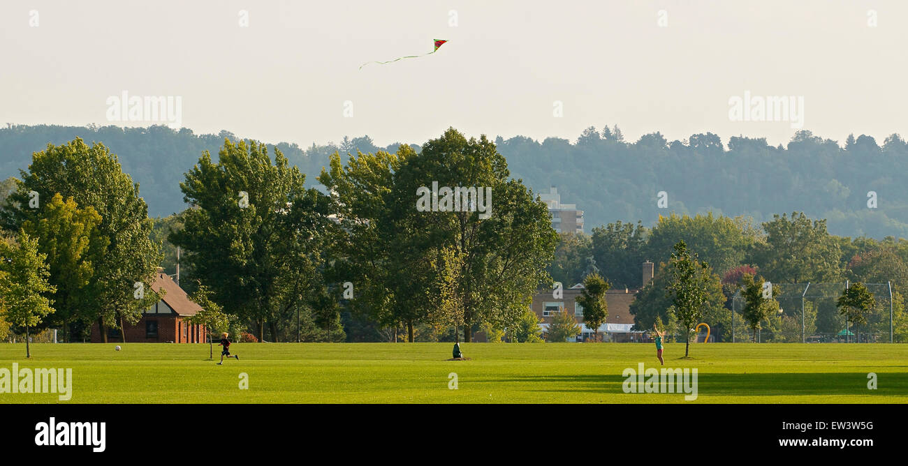 Children playing with the kite and ball on the sunny evening - Stock Image