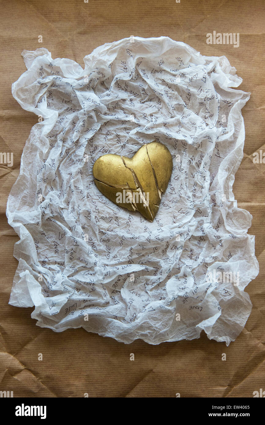 Shattered, gold painted heart on white tissue paper inscribed with the word LOVE.Brown paper background - Stock Image
