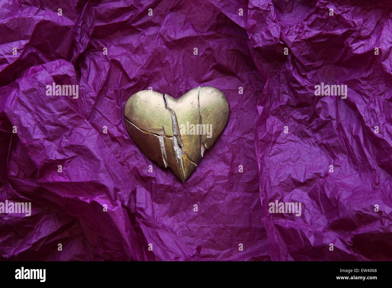 Shattered, gold painted heart on crumpled purple tissue paper. - Stock Image
