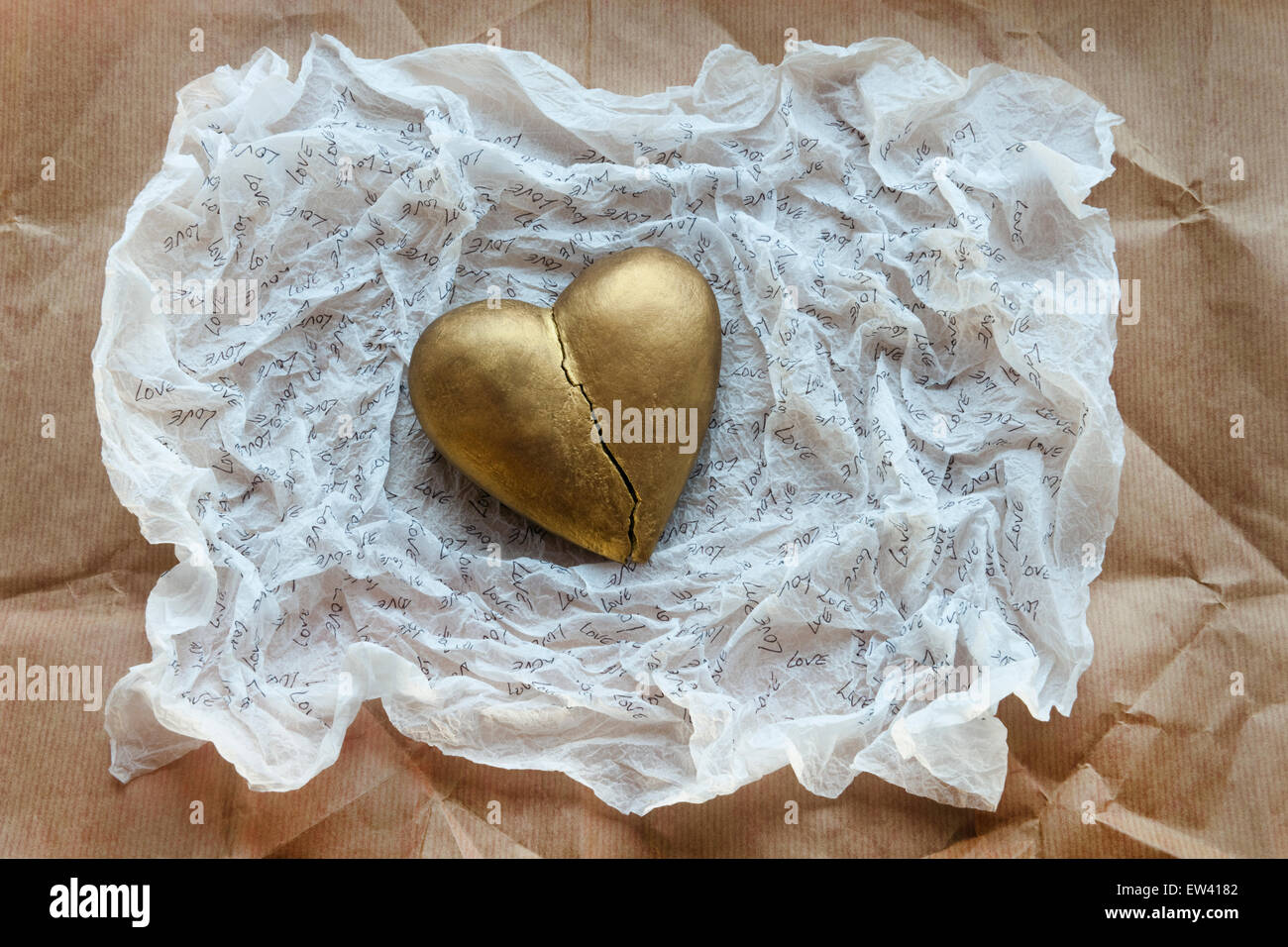 Broken, gold effect heart on white tissue paper inscribed with the word LOVE. Brown paper background - Stock Image