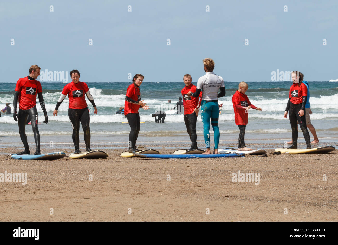 Surfing lessons at a surf school on  the beach at Polzeath Cornwall, UK - Stock Image