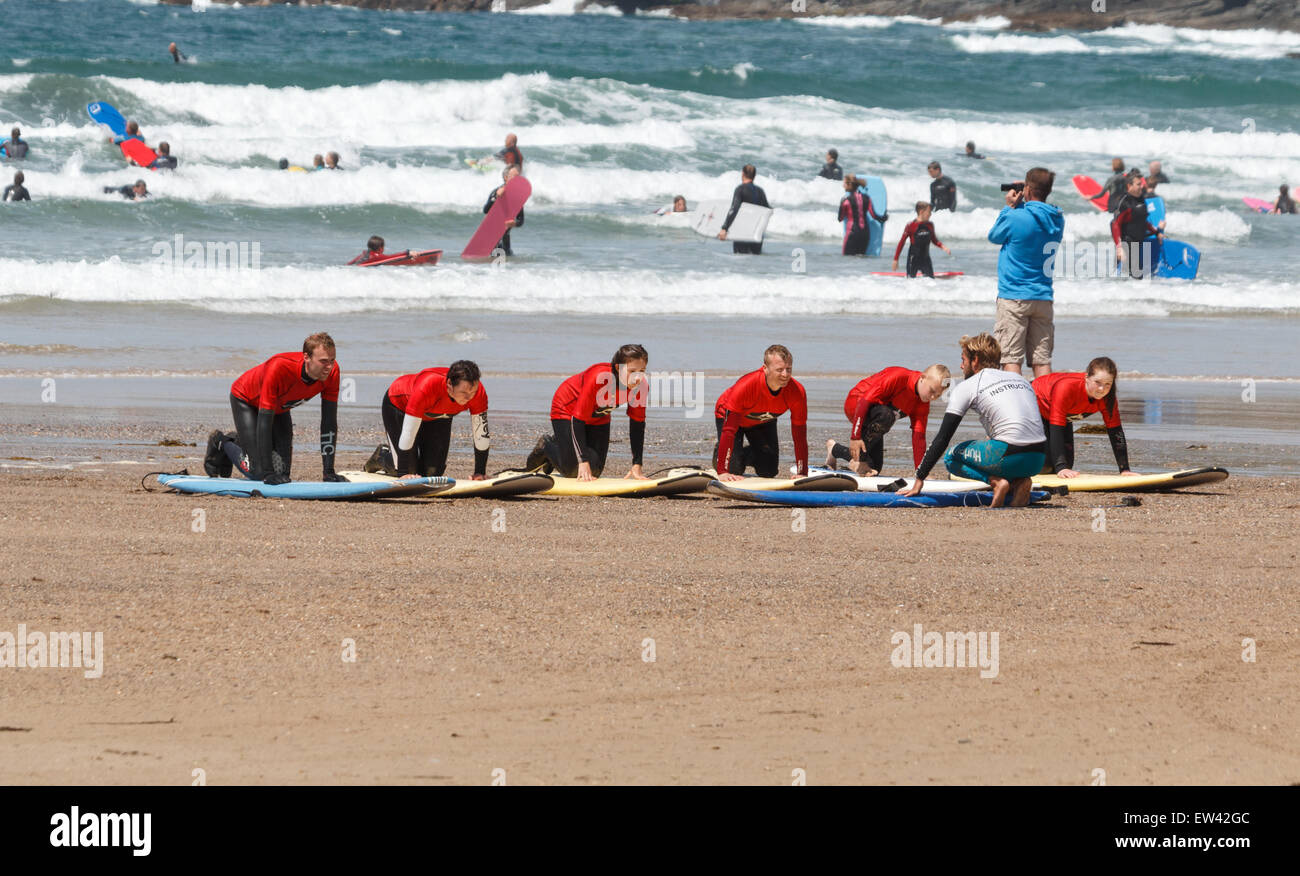 Surf school Surfing lessons on  the beach at Polzeath Cornwall, UK, The students are  kneeling on their surfboards - Stock Image
