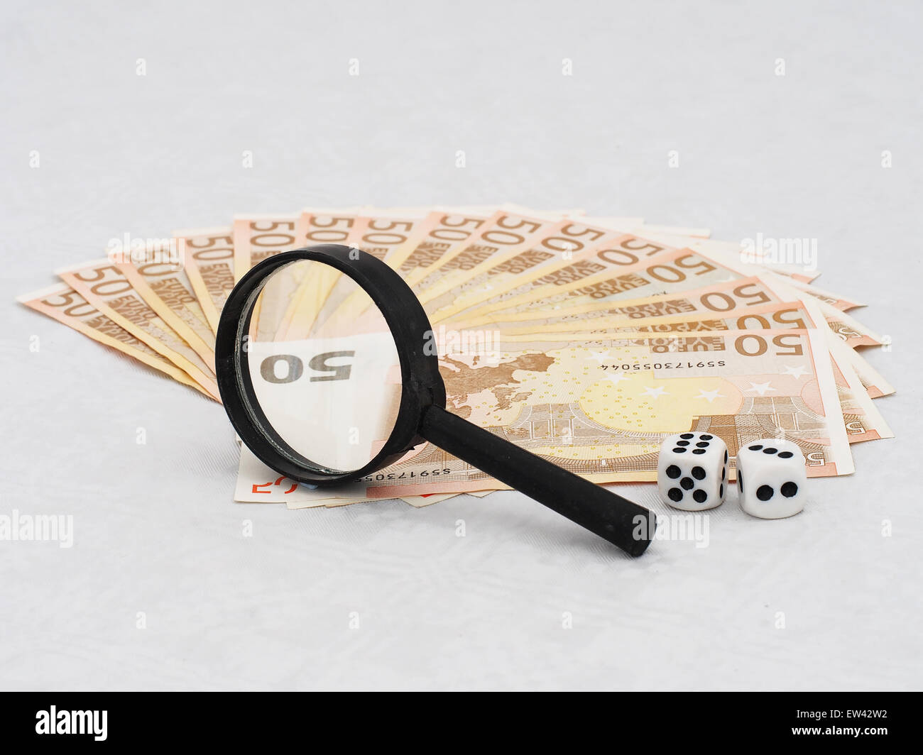 Investing in the Euro concept. Real Euro notes under real magnifying glass with real magnification. - Stock Image