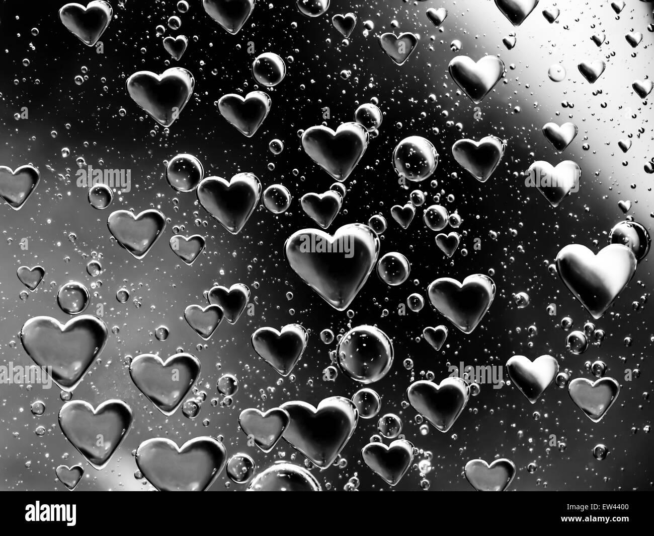 Metallic air bubbles shaped like hearts - Stock Image