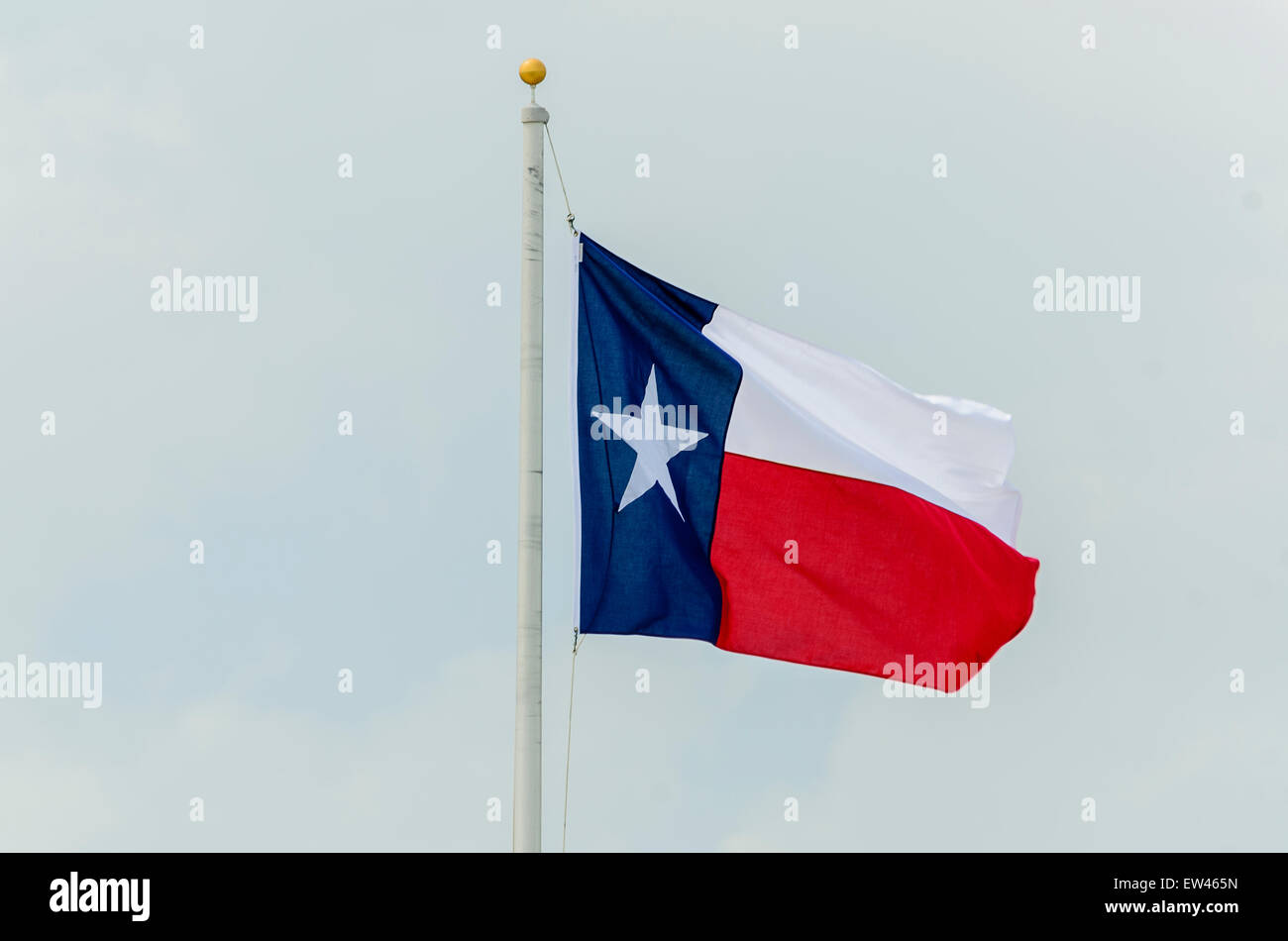 The Texas State flag flying from a flagpole against a pale blue sky. Texas, USA. - Stock Image