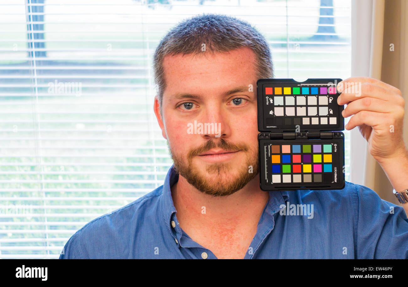 A 28 year old Caucasian man holds an xrite color checker