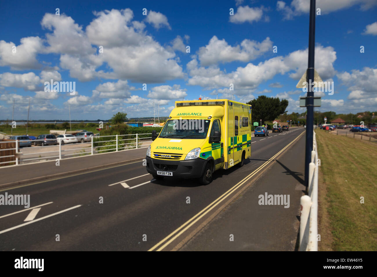 Yellow Emergency Ambulance rushing on single lane road - Stock Image