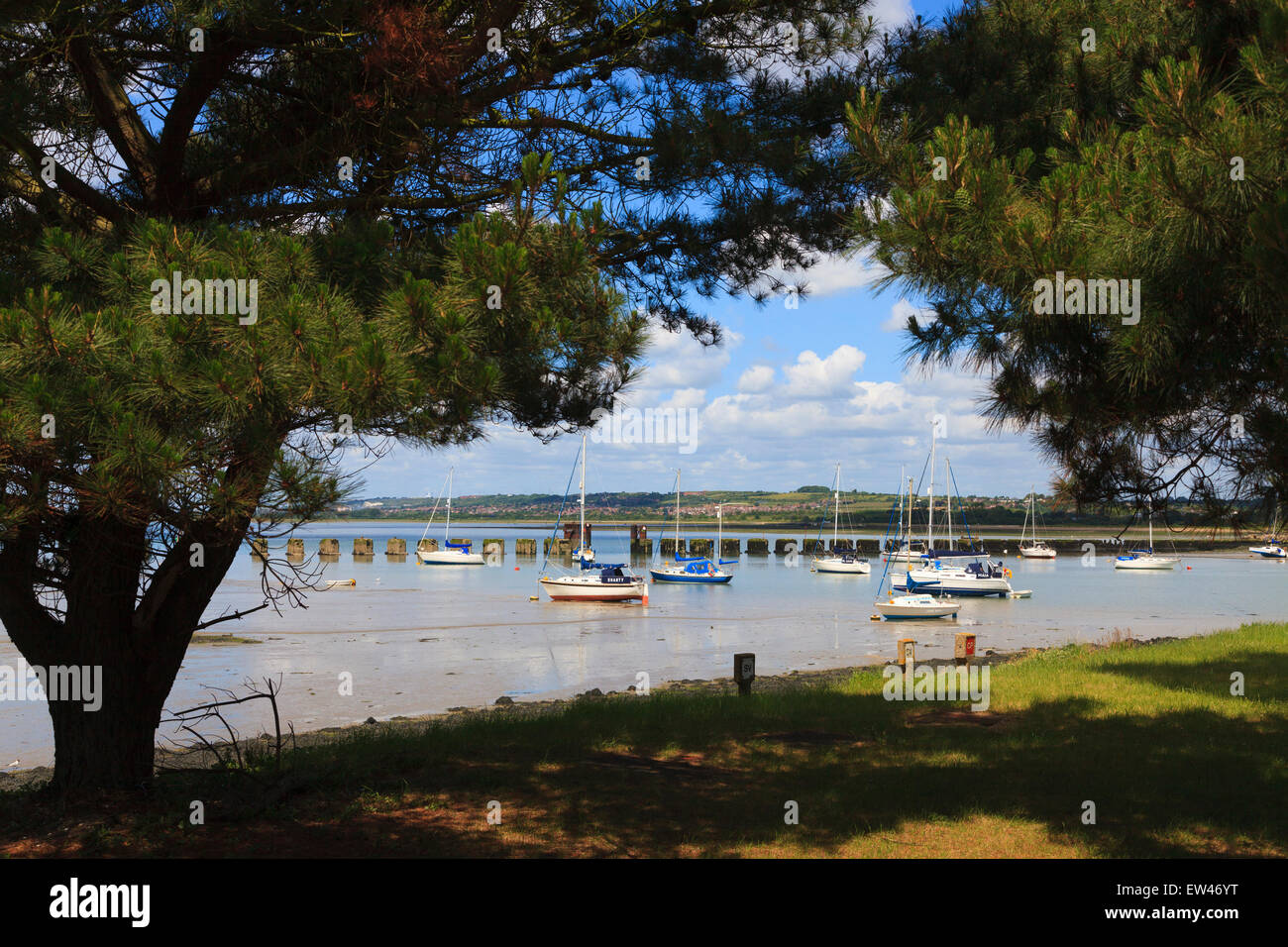 Picturesque picture postcard view of yachts in Langstone Harbour with the remains of the Hayling Billy Bridge Stock Photo