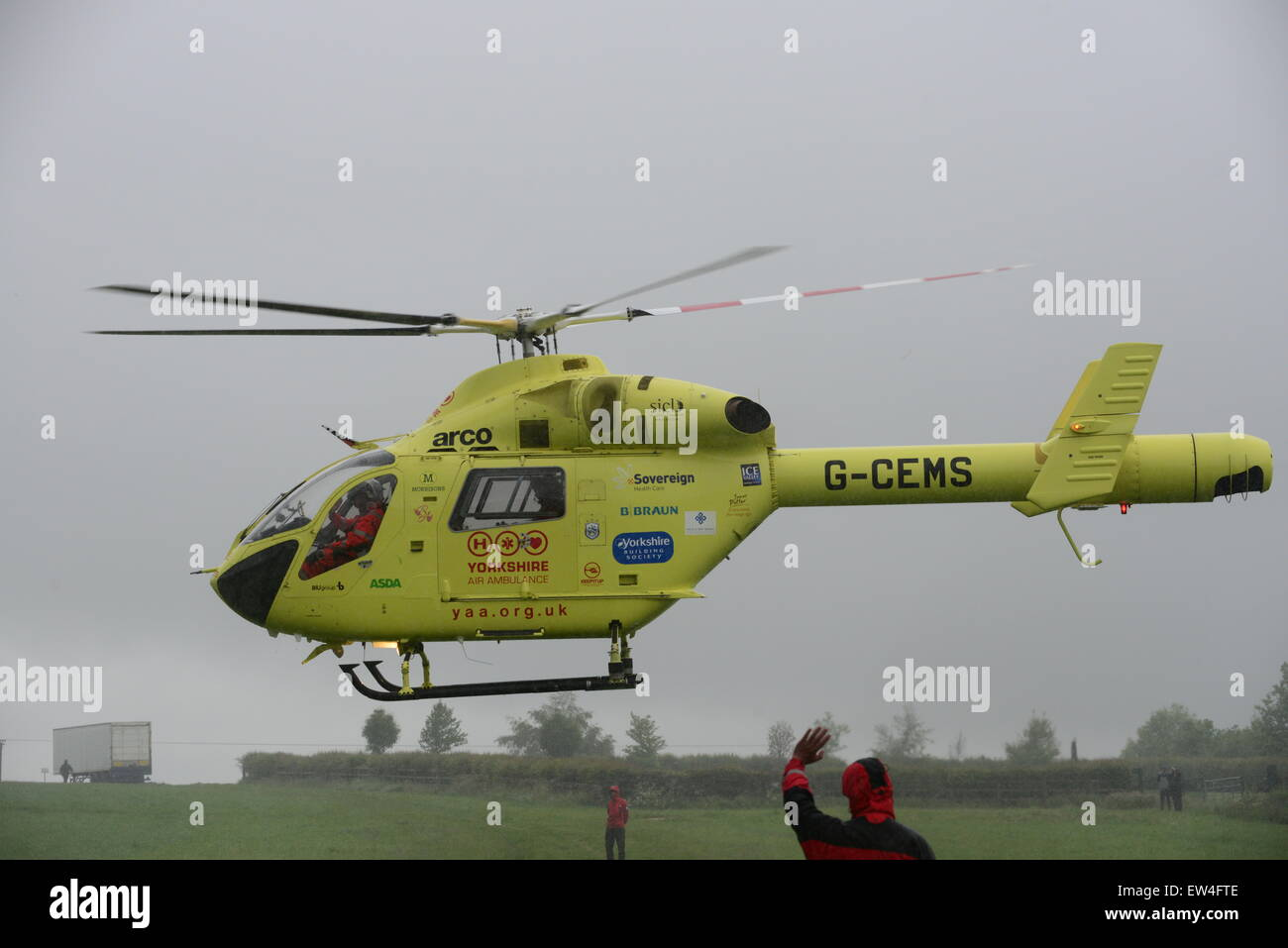Yorkshire Air Ambulance taking off in rainy weather, Barnsley, South Yorkshire, UK. Picture: Scott Bairstow/Alamy - Stock Image