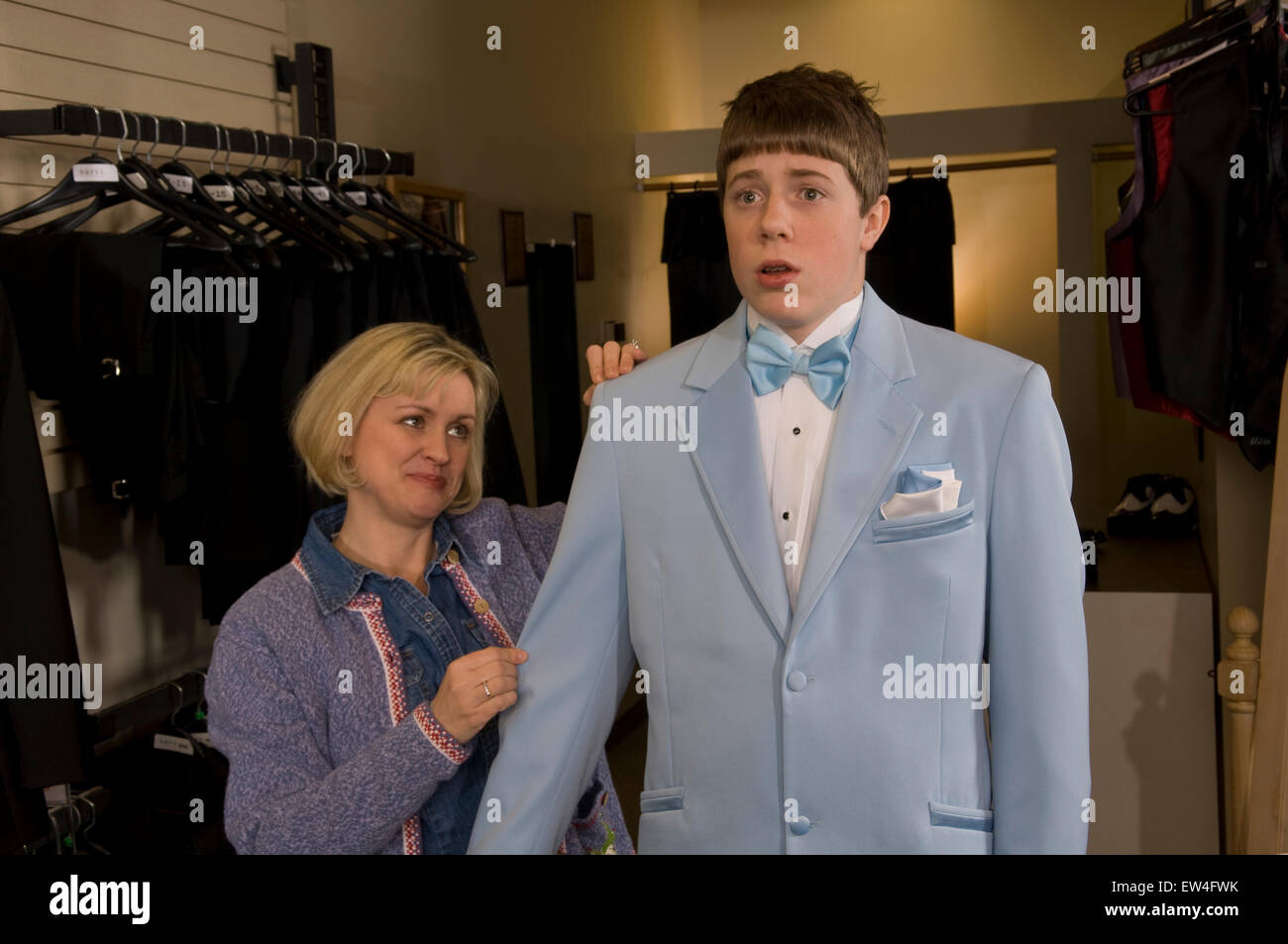 Teenage boy wearing blue suit jacket in tux shop looks worried as his mother adjusts his sleeve Madison Wisconsin. - Stock Image